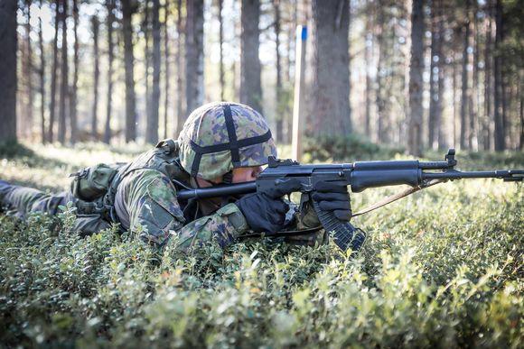 Taistelija makaa maassa ja tähtää rynnäkkökiväärillä.
