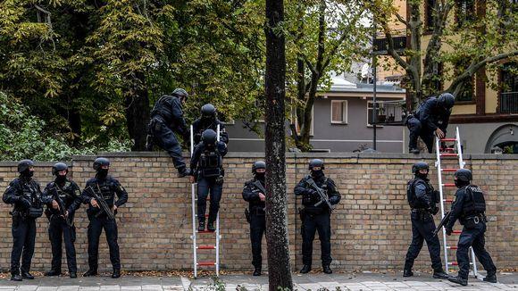 Poliiseja seisoo muurin vierellä. Osa kiipeää tikkaita muurin yli.