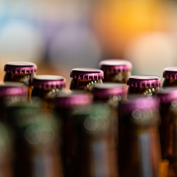 Kruunukorkillisia olutpulloja rivissä.
