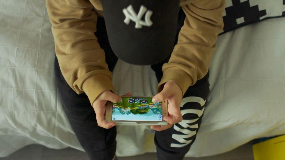Pieni poika, jonka kasvoja ei näy, pelaa älypuhelimella.