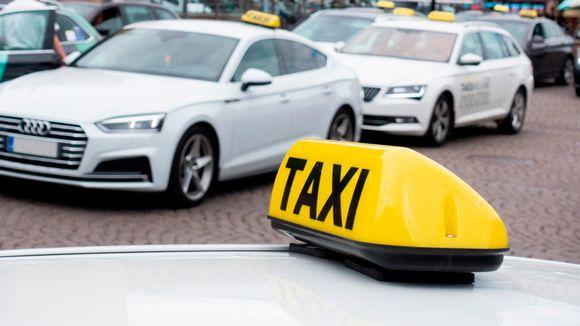 Taksikyltti, taustalla taksiautoja