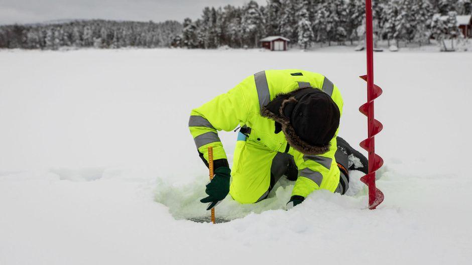 Heimo Pukkila mittaa mittanauhalla tarkasti Inarijärven jäänpaksuutta.