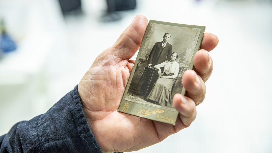 Mies pitää vanhaa valokuvaa kädessään.