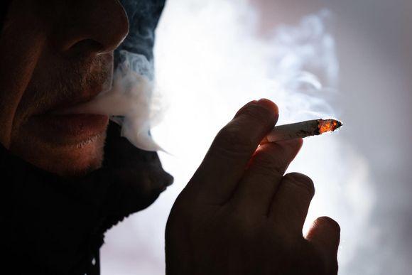 Lähikuvassa silhuettina henkilö polttaa tupakkaa.