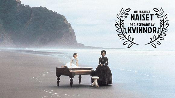 Nainen ja tyttö ja piano autiolla rannalla. Kuvassa iso Ohjaajina naiset -logo. Kuva elokuvasta Piano.