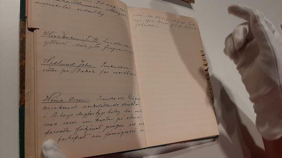 En hand med vit handske bläddrar försiktigt i en gammal anteckningsbok.
