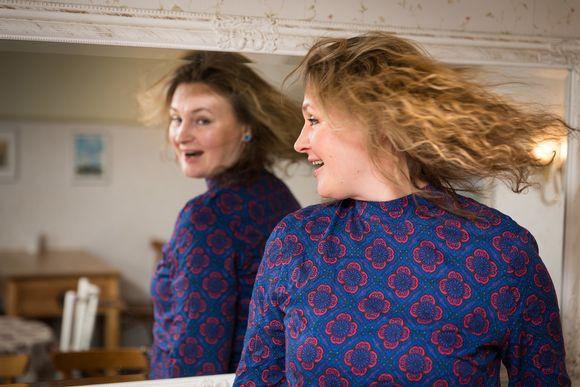 Ria Kataja heilauttaa hiuksiaan peilin edessä.