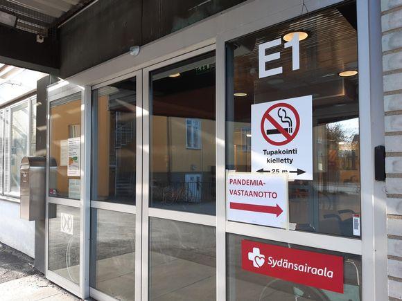 Terveysaseman ovessa on kyltti pandemiavastaanotolle.
