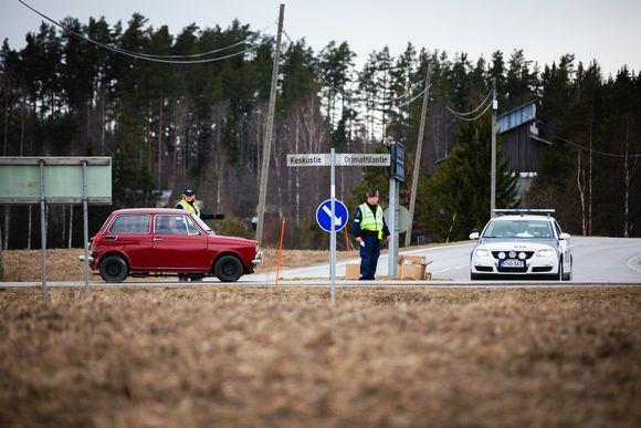 Poliisi pysäyttää auton Pukkilan karanteeni rajalla.