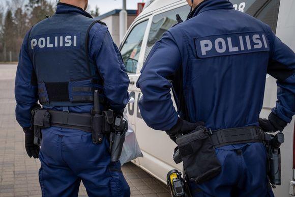 Kaksi järjestyspoliisia takaapäin kuvattuna. Poliisin työssään kokema väkivalta on kasvanut. Kuvituskuva.