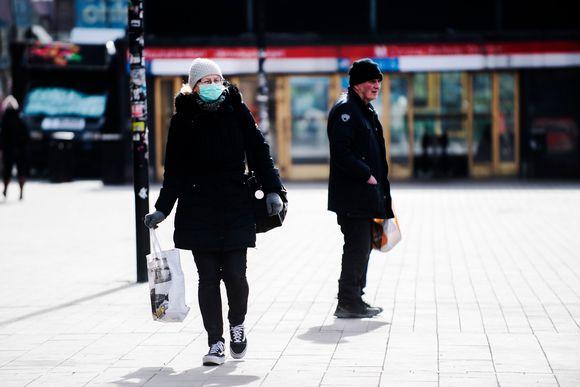 Kuvassa on hengityssuojainta käyttävä nainen, joka kävelee kohti kameraa.