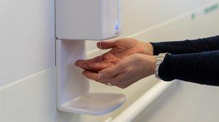 Käsihuuhdeautomaatti ja kädet