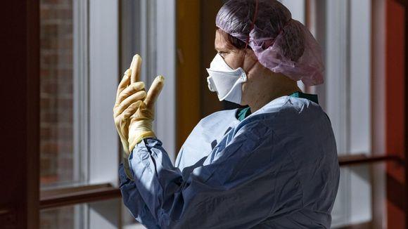 Sairaanhoitaja seisoon ikkunan edessä suojavarusteissa.