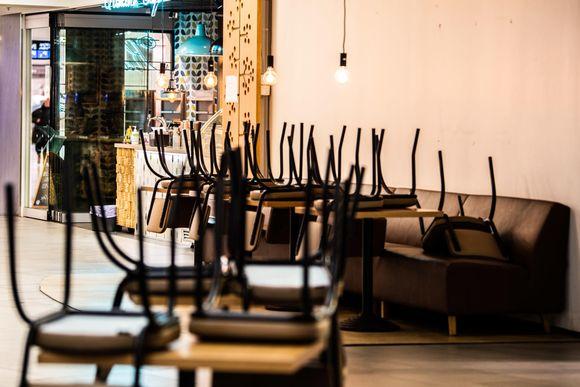 Kahvilan pöytien tuolit pöydillä estämässä asiakkaita istumasta Espoon Tapiolassa.