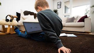 Poika istuu lattialla tietokone sylissään.
