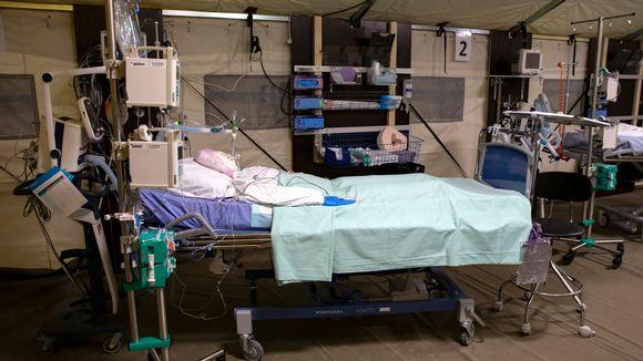 Telttaan rakennettu varasairaala parkkihallissa. Potilasta esittävä kyhäelmä sairaalasängyssä.