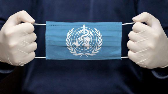 Valkoisiin suojahansikkaisiin puetut kädet pitelevät kasvosuojainta, jossa on sinisellä pohjalla Maailman terveysjärjestön WHO:n valkoinen logo.