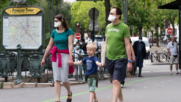 äiti, isä ja lapsi kävelevät metroaseman edessä