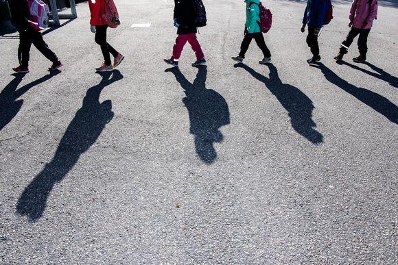 Kuvassa koululaiset kulkevat jonossa turvavälien kera.