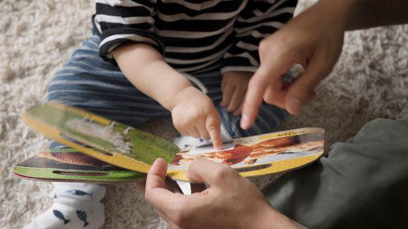 Lapsi katselee kuvakirjaa vanhempansa kanssa.