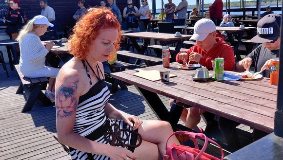 Ihmisiä kesäterassilla juomassa kavhia ja syömässä pannaria, takana jonotetaan tiskille.