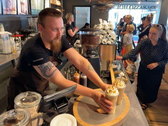 Kokkolan Espresso Housen työntekijä ojentaa kaksi take away -kahvia tiskille.