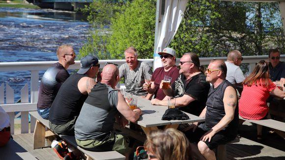 Miehiä istumassa terassipöydässä Rovaniemellä, taustalla tulviva Kemijoki.