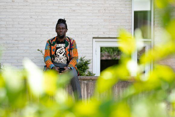 Kuvassa on tutkija Aminkeng Atabong Alemanji istuu betoniaidalla, etualalla lehtiä.