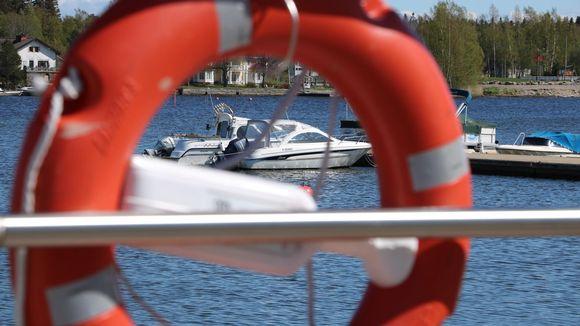 Två båtar skymtar genom en röd livboj.