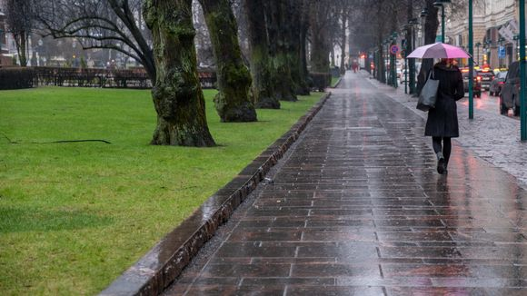 Nainen kävelee sateessa sateenvarjon kanssa Pohjoisesplanadia pitkin.