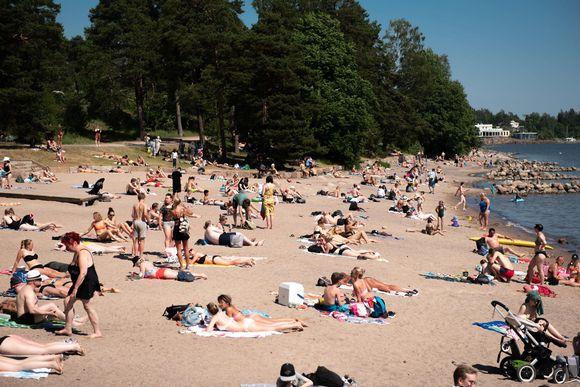 Ihmisiä ottamassa aurionkoa Mustikkamaan uimarannalla.