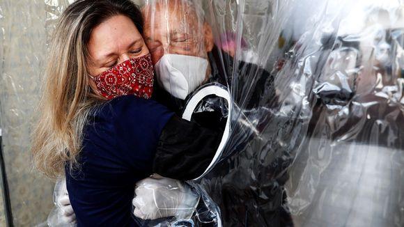 Nainen halaa isäänsä suojaverhon läpi Brasilian Sao Paulossa 2. heinäkuuta 2020.