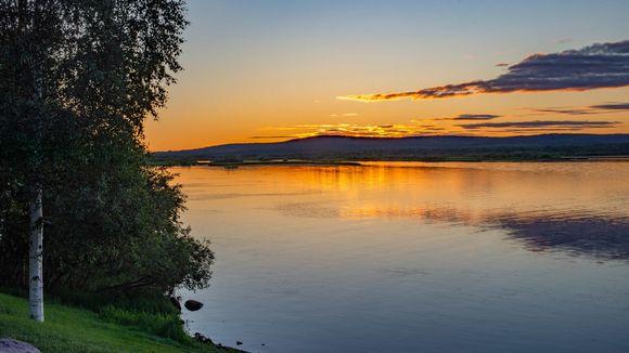 Maisema Ounas- ja Kemijokien risteykseen Rovaniemellä, keskiyön aurinko paistaa.