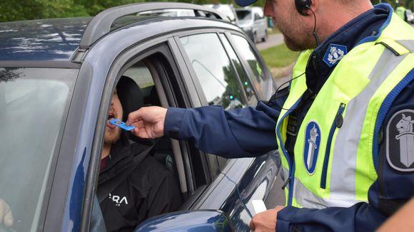 Poliisi tekee huumepikatestiä auton kuljettajalle.
