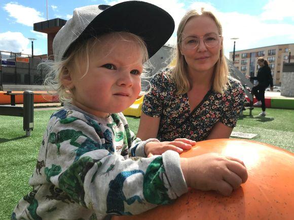 Lapsi leikki puistossa äitinsä kanssa.