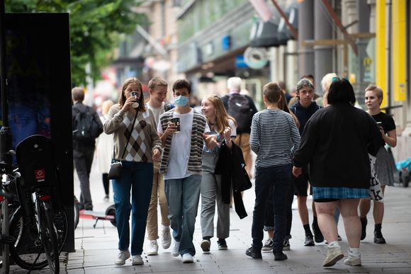 Joukko nuoria kävelee kadulla, yhdellä heistä on päällä kasvomaski.