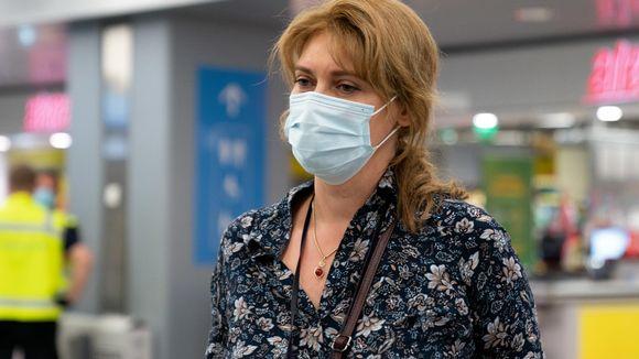 Nainen puhuu toimittajalle maski päässä.