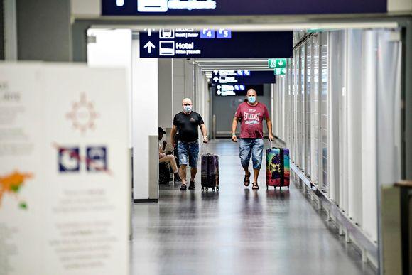 Kaksi matkustajaa kävelee matkatavaroidensa kanssa Helsinki-Vantaan lentoasemalla 7. elokuuta 2020. Kasvojensa edessä heillä on kasvomaskit.