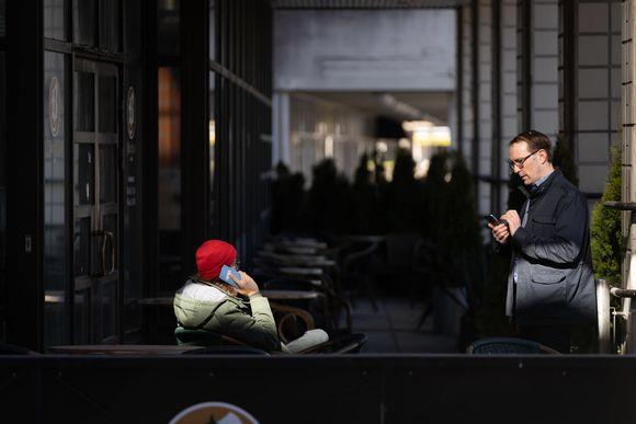 Kaksi Ylen toimittajaa käyttää kännyköitä.