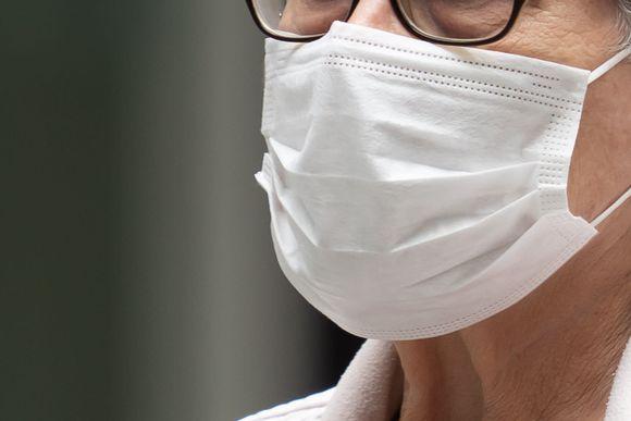 Ihmisen kasvoilla on nenän ja suun peittävä valkoinen hengityssuojain