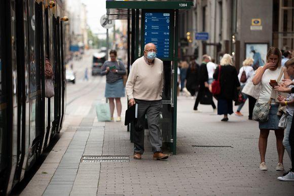 Vanha mies kävelee raitiovaunusta ulos raitiovaunusta kasvomaski päässään.