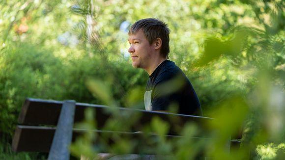 Joni Savolainen istuu puistonpenkillä.