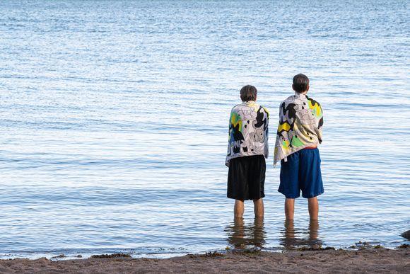 Kaksi miestä rantavedessä kuivattelemassa pyyhkeet harteillaan.