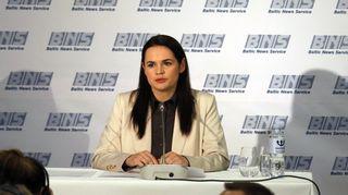 Svjatlana Tsihanouskaja pitää tiedotustilaisuutta vaaleassa jakussa ja mustassa puserossa. Taustalla on kangas, jossa komeilevat Baltic News Servicen tunnukset.