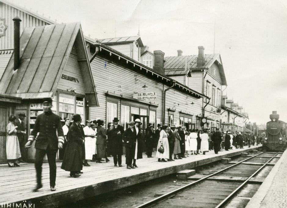 Riihimäen rautatieasema 1920-luvulla. Höyryveturi saapuu. Paljon ihmisiä asemalaiturilla.
