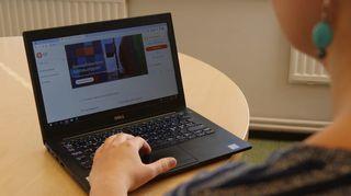 Kannettava tietokone pöydällä, jossa verkkopankki auki.Naisen käsi näppäimistöllä.