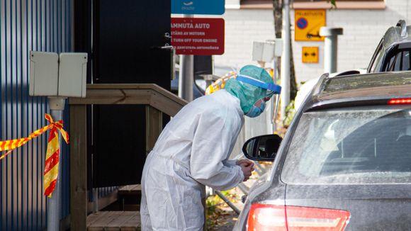 Hoitaja puhuu autossa olevalle asiakkaalle Eksoten drive-in koronanäytteenottopisteessä.