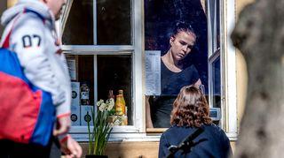 En kvinna säljer kaffe i ett fönster.