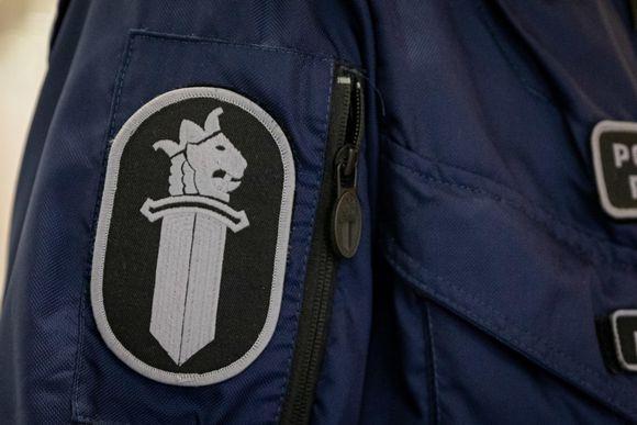 Poliisin virkamerkki työhaalarin hihassa