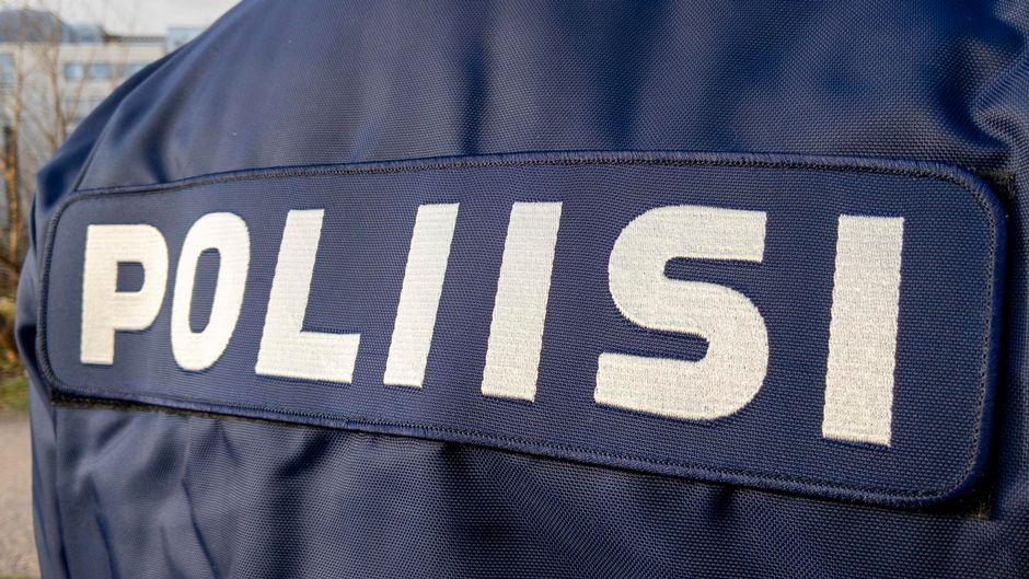 Poliisi teksti poliisihenkilön selässä.